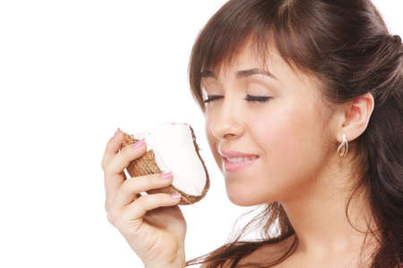 Pretty young brunette woman smelling coconut eyes closed Stock Photo - 5918081