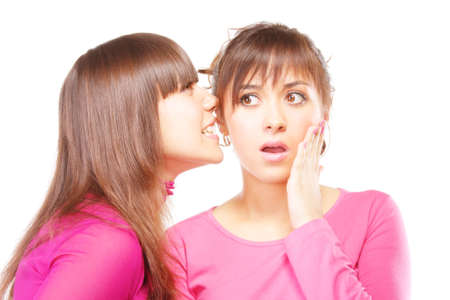 shocking: Young woman in pink whispering shocking news to friend