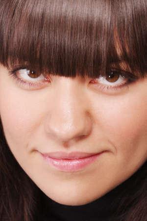 gaze: Jonge brunette vrouw blik van onder fringe close-up foto