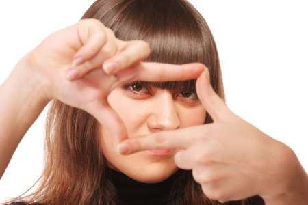 intent: Intent gaze through finger frame of young brunette woman