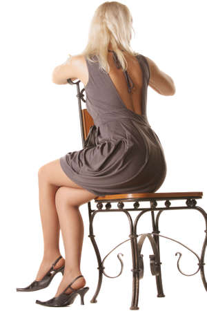 sitting: Woman in gray dress sitting on chair turned away