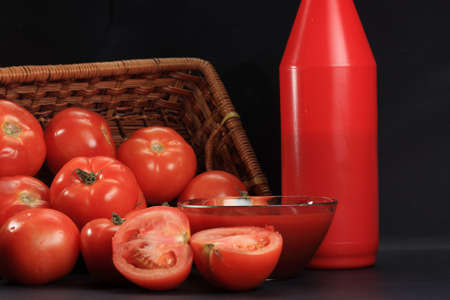 sause: Spread tomatoes and ketchup in a bowl against dark background Stock Photo