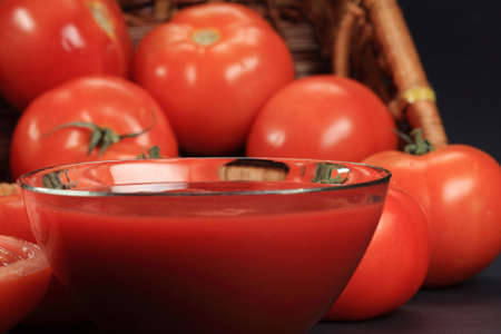 Ketchup in glass bowl with tomatoes on background closeup selective focus Stock Photo - 6036358