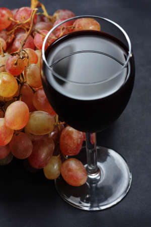 Red wine in glass and bunch of grapes over dark background photo