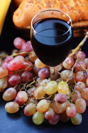 Glass of red wine covered with grapes with pastry on background photo