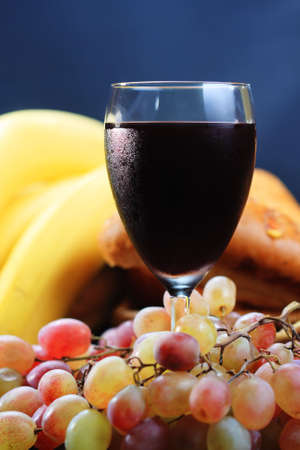 Glass of cold red wine with bananas on background photo