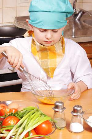paliza: Ni�o de cocinero poco batiendo hasta huevos en bol de cristal Foto de archivo