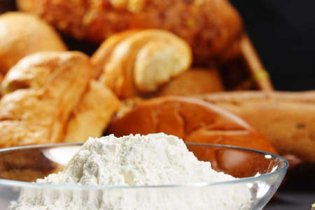 Flour in glass bowl and bread on background selected focus Stock Photo - 6091678