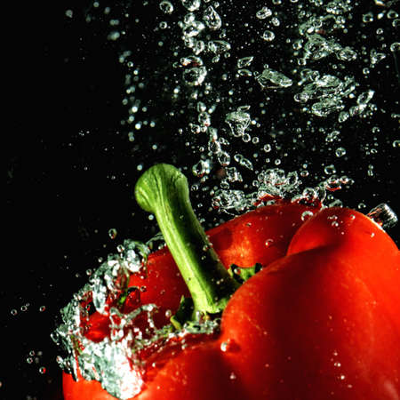 Red paprika pepper and water bubbles against dark background