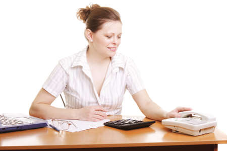 answer phone: Young woman sitting at desk waiting for phone answer Stock Photo