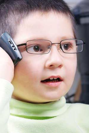 Little boy in green have thrilling phone talk photo