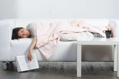 Young brunette woman having afternoon nap on white sofa Stock Photo