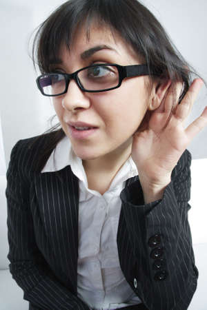 eavesdropping: Eavesdropping brunette businesswoman closeup photo in espionage concept