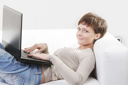 Young smiling woman laying down on white sofa with computer photo