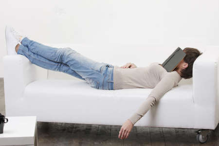 Young woman having afternoon nap with book on face photo