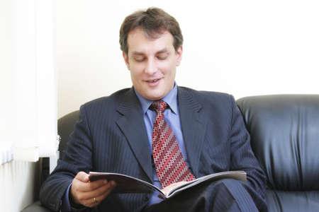 Smiling businessman reading magazine while sitting on leather sofa Stock Photo