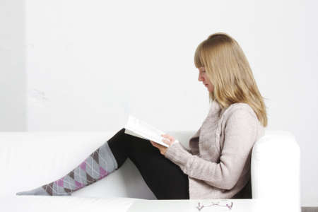 cardigan: Young blonde woman reading book sitting on sofa sideview