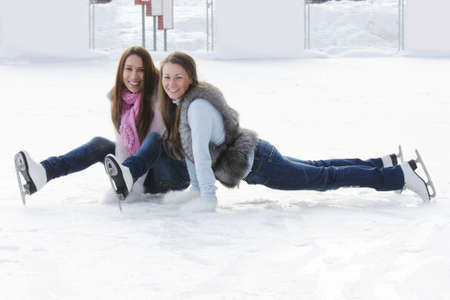 Two young smiling women on ice rink in winter day Stock Photo