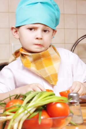 perplexity: Little cook boy in perplexity standing at kitchen selective focus