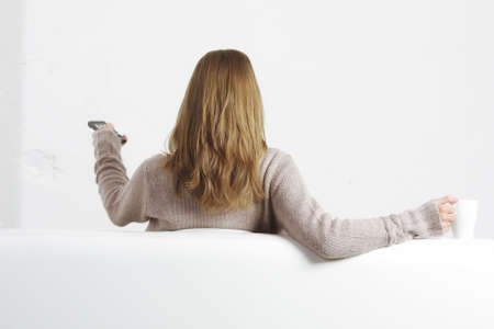 Young blonde woman sitting on sofa with remote control rear view photo