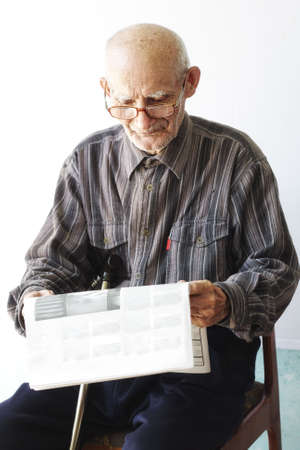 Senior man in eyeglasses with newspaper sitting on chair outdoors photo