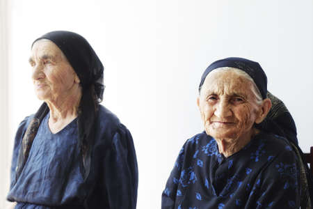Two elderly women sitting against light wall selective focus Stock Photo - 6376680