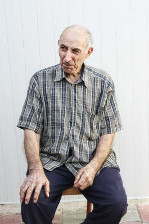 Serious elderly man in striped shirt sitting on chair Stock Photo - 6376690