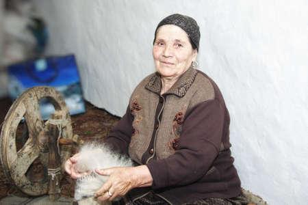 carding: Senior woman carding woollen yarn siiting on floor indoors Stock Photo
