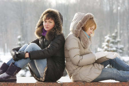 parapet: Two young woman sitting on stone parapet have serious talk