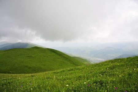 over the hill: Nubes bajas lluvias sobre hill en verano del C�ucaso mauntains