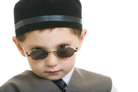 reproach: Little boy in black cup looking over sunglasses with reproach