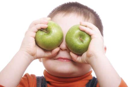 shutting: Boy shutting eyes with apples loseup photo against white