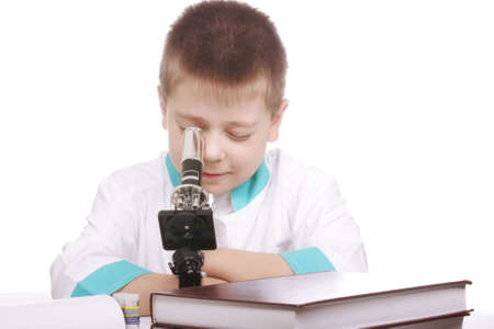 smock: Boy in lab smock looking into microscope against white background Stock Photo