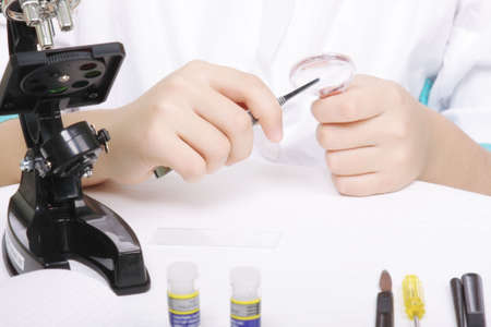 Hands with magnifier and tweezers at researcher desk closeup photo Stock Photo - 6644867