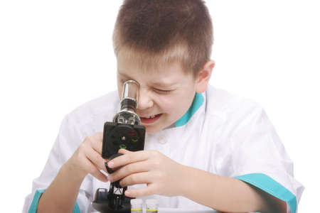 smock: Kid in lab smock looking into microscope against white background Stock Photo