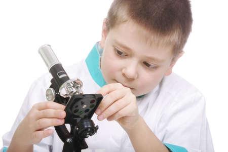 smock: Kid in lab smock adjusting microscope photo against white
