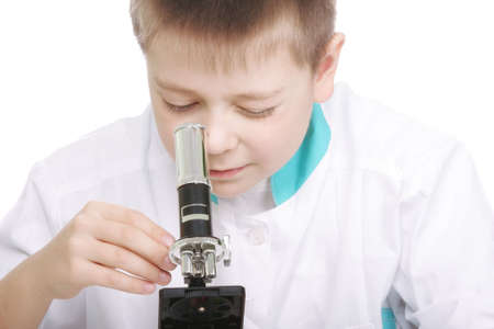 smock: Kid in lab smock tuning microscope against white background Stock Photo