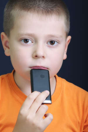 Pensive kid in orange with cellphone against dark background Stock Photo