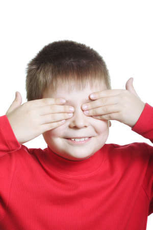 shutting: Smiling boy in red shutting eyes photo against white