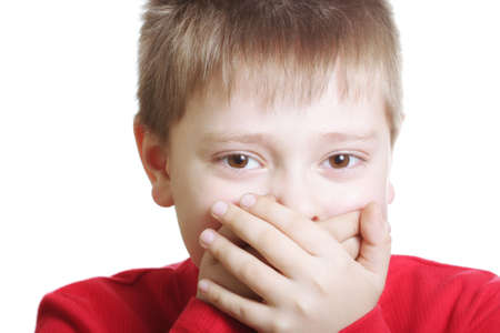 shutting: Boy in red shutting mouth with hands against white background Stock Photo