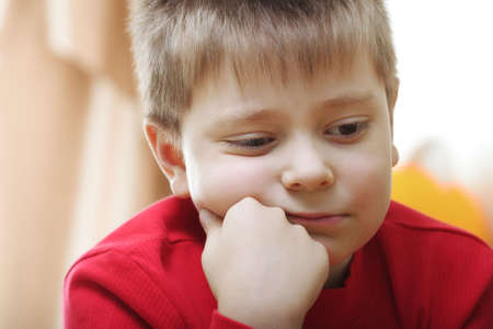 Thoughtful kid in red leaning on fist closeup photo
