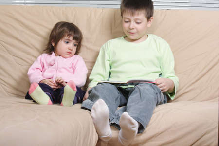 Boy reading book to girl sitting on brown sofa photo
