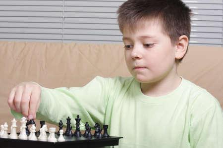 Boy in green shirt playing chess sitting on brown sofa photo