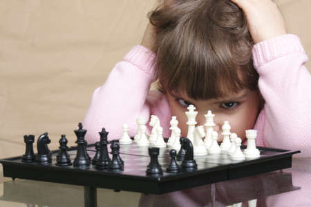 Little girl in pink thinking over chess game closeup  Stock Photo