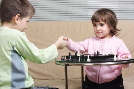 Chess playing children shaking hands after match Stock Photo