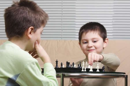 Two kids playing chess sitting on brown sofa