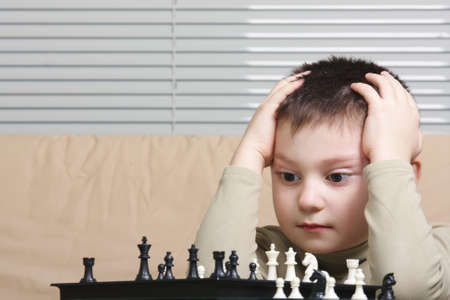 Little thoughtful chess player embracing head closeup