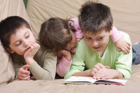 Three children reading book laying on brown sofa photo