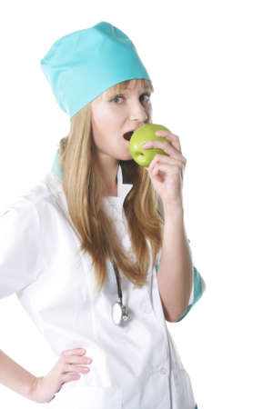 Young doctor biting green apple against white background photo