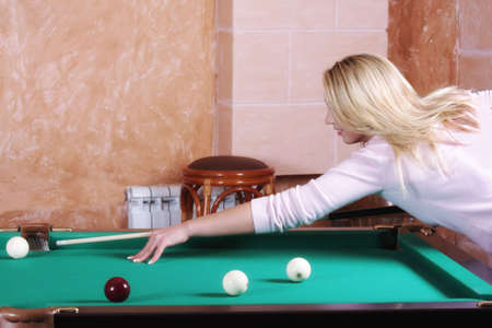 Young blond woman in pink sweater playing pool  photo